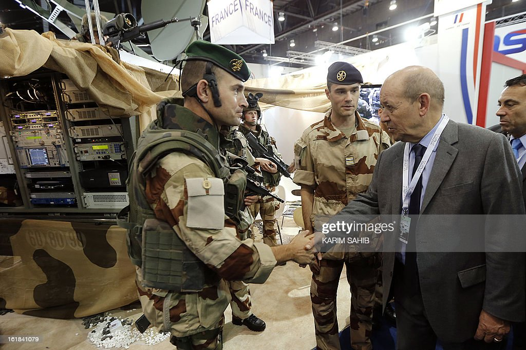 French Defence Minister Jean-Yves Le Drian (R) meets with French troops during the opening of the International Defence Exhibition and Conference (IDEX) at the Abu Dhabi National Exhibition Centre in the Emirati capital on February 17, 2013. A top French defence industry official said that talks to sell Rafale jet fighters to the UAE were 'progressing well', expressing confidence that a deal could be reached with the Gulf state. AFP PHOTO/KARIM SAHIB