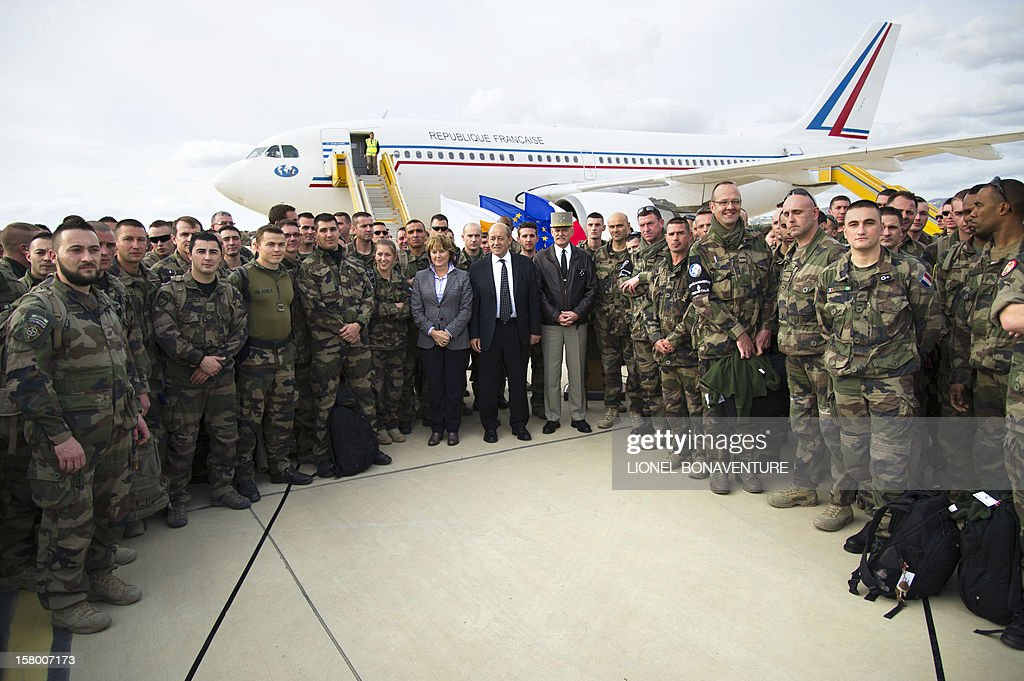 French Defence Minister, Jean-Yves Le Drian (C), national assembly's defense commission President Patricia Adam and General Clement-Bolle pose with French soldiers Paphos airport in Cyprus in December 8, 2012 before leaving for France. Le Drian today welcomed some 150 French soldiers returning from Afghanistan.