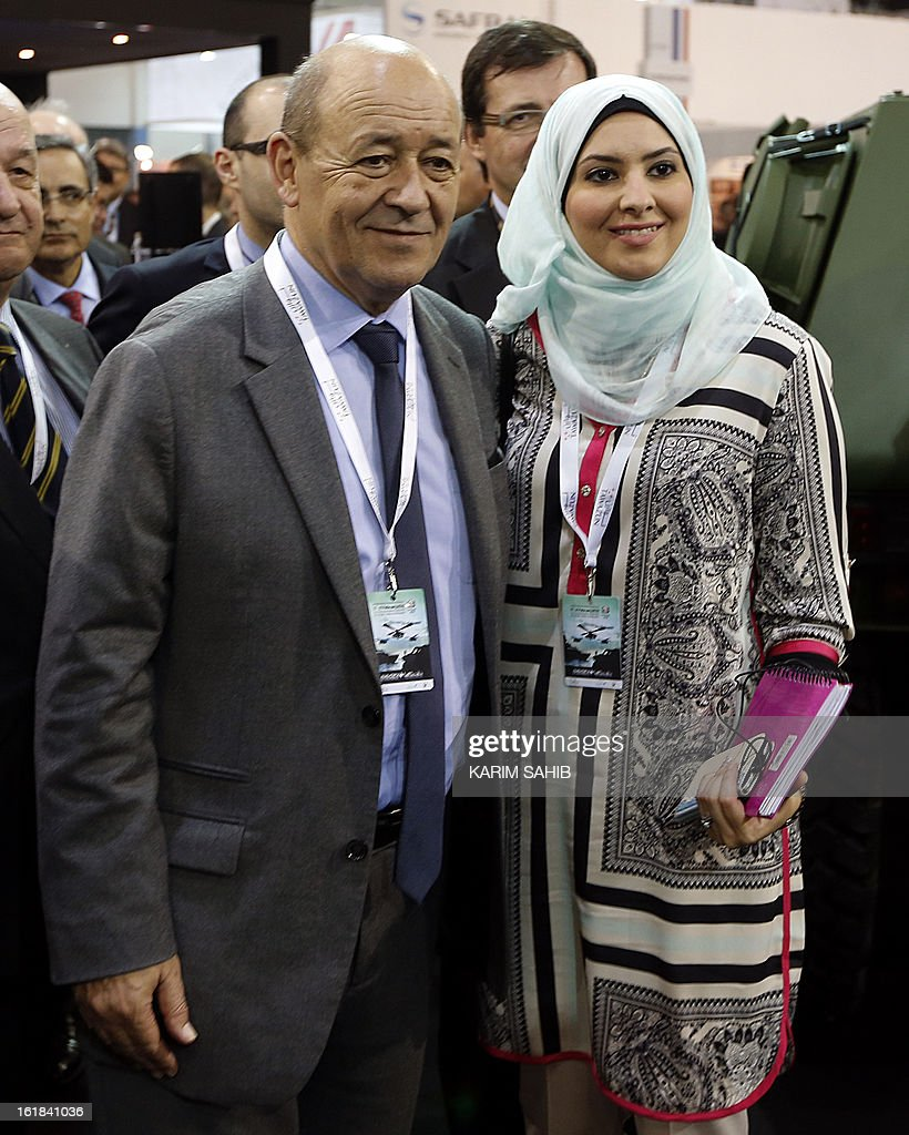 French Defence Minister Jean-Yves Le Drian (L) poses for a picture with a woman attending the opening of the International Defence Exhibition and Conference (IDEX) at the Abu Dhabi National Exhibition Centre in the Emirati capital on February 17, 2013. A top French defence industry official said that talks to sell Rafale jet fighters to the UAE were 'progressing well', expressing confidence that a deal could be reached with the Gulf state.