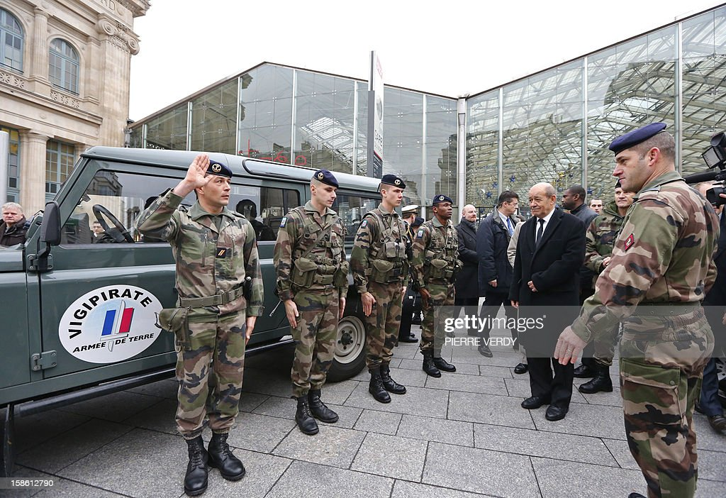 French Defence Minister Jean-Yves Le Drian (2ndR) reviews security forces deployed on December 21, 2012 at Gare du Nord railway station in Paris as France's national security alert system 'Plan Vigipirate' is reinforced for the Christmas holidays .