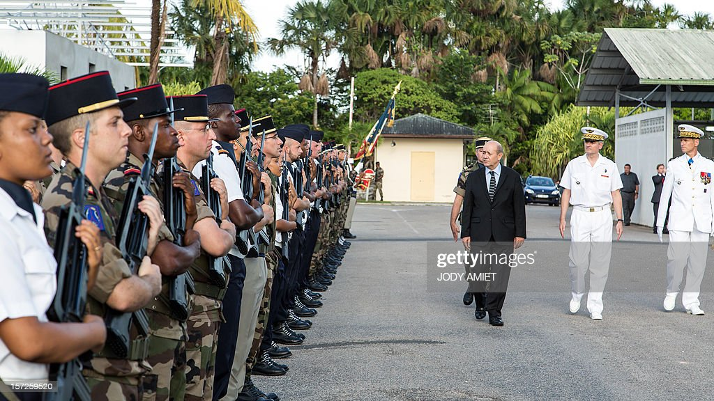 French Defence Minister Jean-Yves Le Drian (C) revues an honor guard at the air-base 367 in Cayenne, French overseas region of Guiana, on November 30, 2012, as part of a three-day visit.