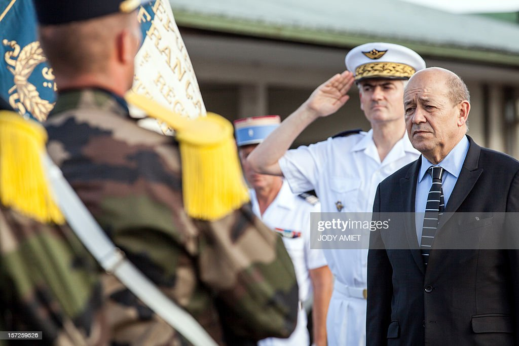 French Defence Minister Jean-Yves Le Drian (R) revues an honor guard at the air-base 367 in Cayenne, French overseas region of Guiana, on November 30, 2012, as part of a three-day visit.