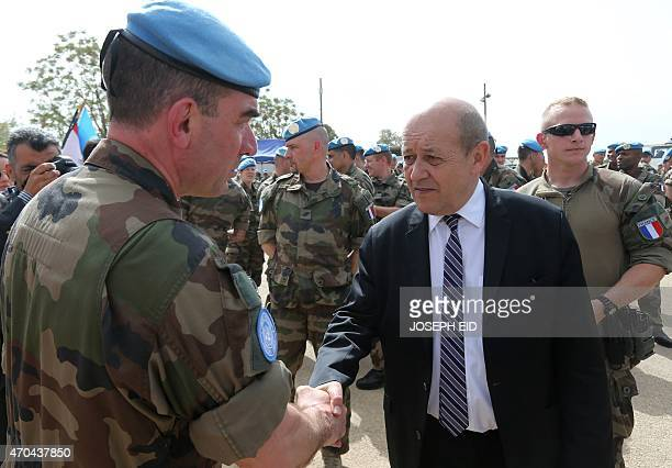 French Defence Minister JeanYves Le Drian shakes hands with a French soldier of the United Nations Interim Forces in Lebanon during a visit to the...