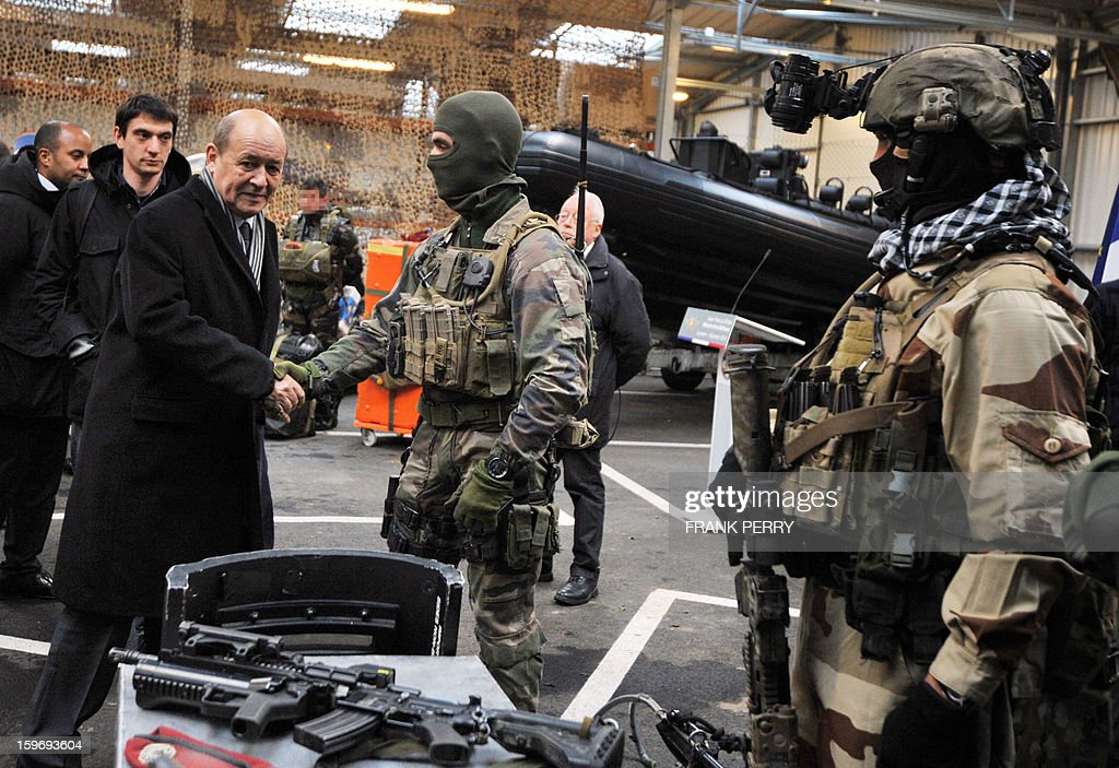 French Defence Minister Jean-Yves Le Drian (L) shakes hands with a member of the French special forces during his visit to a sniper commando base on January 18, 2013 in the northwestern French town of Lanester.