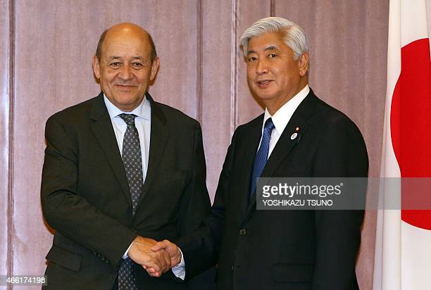 French Defence Minister JeanYves Le Drian shakes hands with his Japanese counterpart Gen Nakatani prior to their talks at the Defense Ministry in...