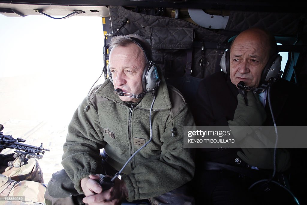 French Defence Minister Jean-Yves Le Drian (R) sits next to French commander in Afghanistan, General Olivier de Bavinchove in a military helicopter flying above Kabul on January 01, 2013.