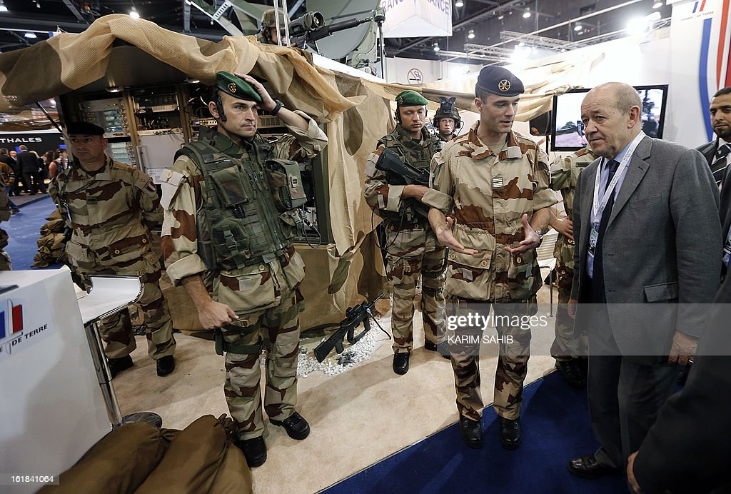French Defence Minister Jean-Yves Le Drian (R) speaks with French troops during the opening of the International Defence Exhibition and Conference (IDEX) at the Abu Dhabi National Exhibition Centre in the Emirati capital on February 17, 2013. A top French defence industry official said that talks to sell Rafale jet fighters to the UAE were 'progressing well', expressing confidence that a deal could be reached with the Gulf state.