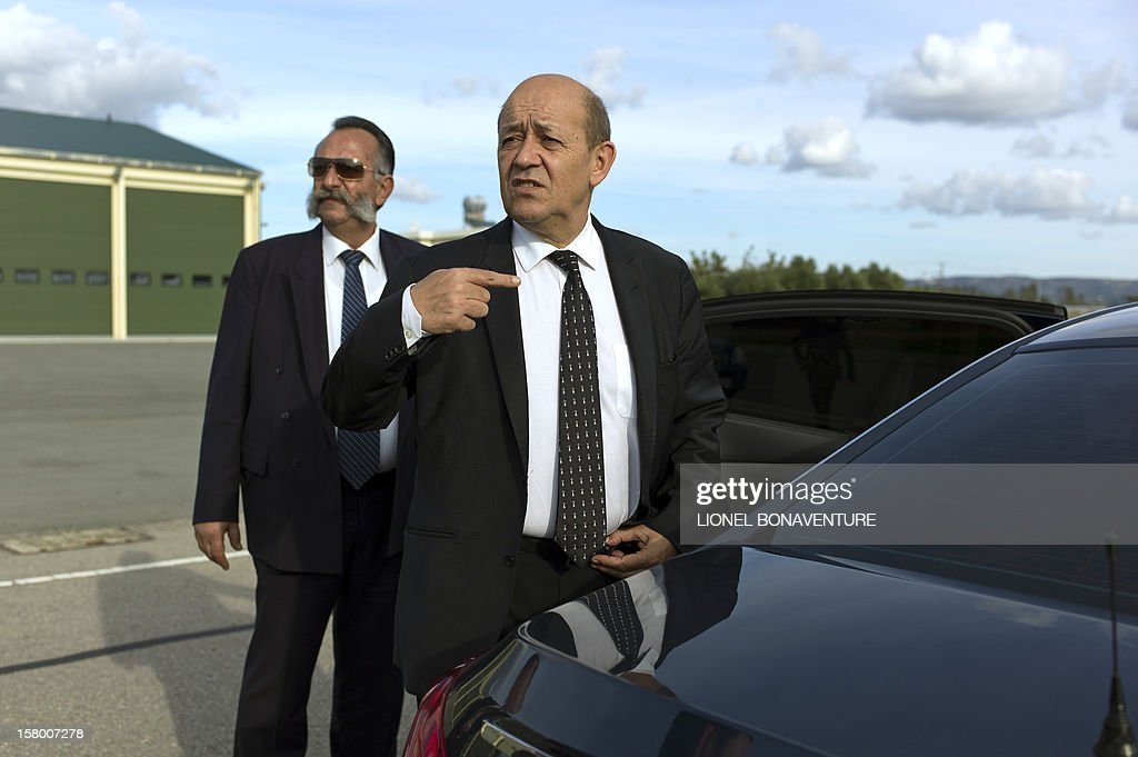 French Defence Minister, Jean-Yves Le Drian (C) stands at Paphos airport in Cyprus in December 8, 2012 before leaving for France. Le Drian today welcomed some 150 French soldiers returning from Afghanistan.