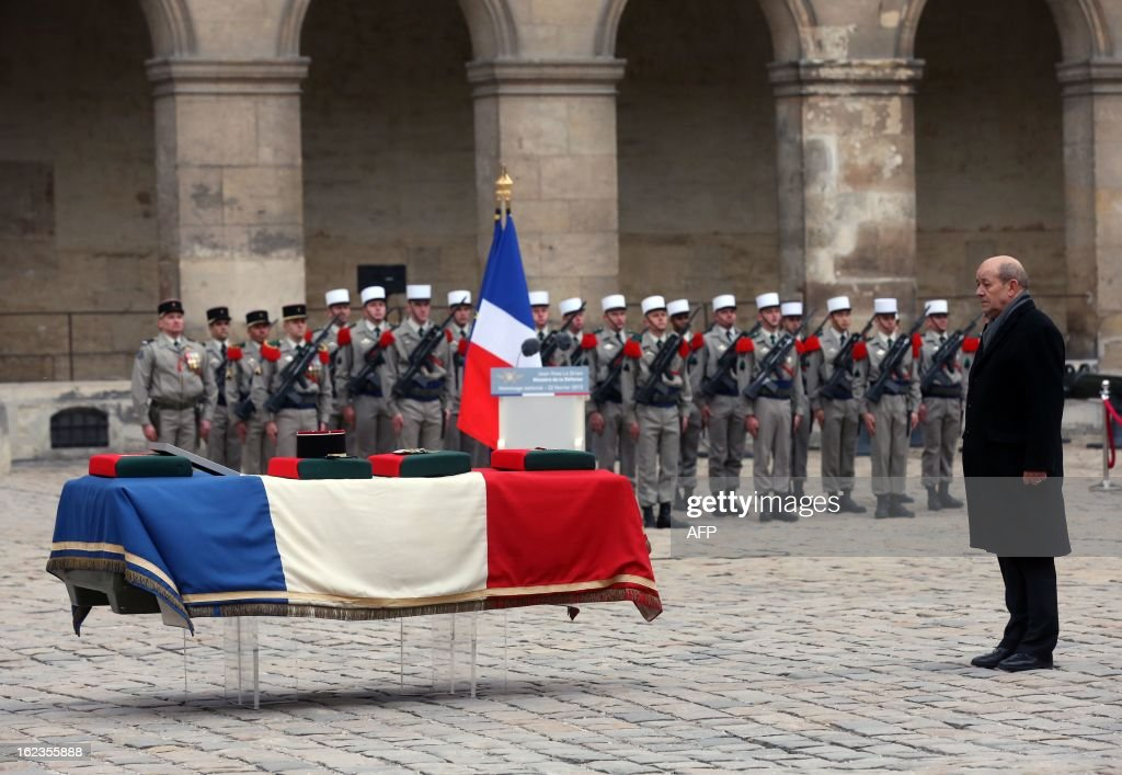French Defence minister Jean-Yves Le Drian stands in front of the coffin of French Staff Sergeant Harold Vormezeele during an official ceremony held in the Hotel des Invalides courtyard on February 22, 2013 in Paris. Vormezeele, a NCO and commando with the 2nd Foreign Parachute Regiment, an elite unit of the French Foreign Legion, was killed on February 19 during an operation in northern Mali against Islamist rebels. He was the second French soldier killed since the start of France's military intervention in Mali on January 11.