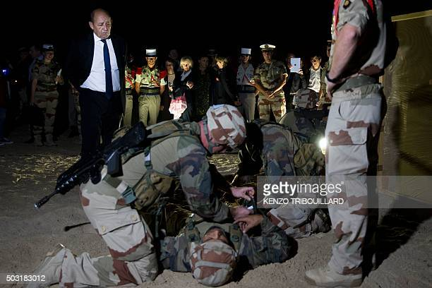 French Defence minister JeanYves Le Drian stands next to soldiers of the 13th DemiBrigade of the Foreign Legion during a visit to the military base...
