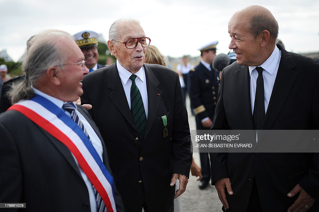 French Defence Minister, Jean-Yves Le Drian (R) talks to French former member of the resistance and 'Compagnon de la Liberation' Fred Moore (C) during a ceremony to pay homage to the Force Française Libres (Free French forces) who fought the nazis during the second world war on August 30, 2013 at the Ile-de-Sein (Sein Island), western France.
