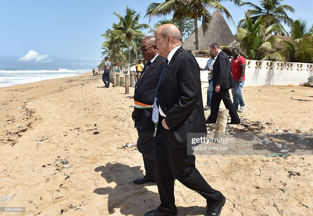 French Defence Minister Jean-Yves Le Drian (R) walks with Deputy Mayor of Grand-Bassam Guy Daniel Ouegnin, after laying wreaths in homage to the victims of a jihadist attack, on the beach of the Hotel l'Etoile du Sud in Grand Bassam on April 30, 2016. France will increase the number of its troops in Ivory Coast, Defence Minister Jean-Yves Le Drian said on a trip to the African nation which hosts a regional base for French forces. / AFP / ISSOUF