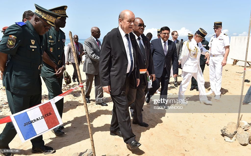 French Defence Minister Jean-Yves Le Drian (C) walks with Deputy Mayor of Grand-Bassam Guy Daniel Ouegnin (C-R) after laying wreaths in homage to the victims of a jihadist attack, on the beach of the Hotel l'Etoile du Sud in Grand Bassam on April 30, 2016. France will increase the number of its troops in Ivory Coast, Defence Minister Jean-Yves Le Drian said on a trip to the African nation which hosts a regional base for French forces. / AFP / ISSOUF