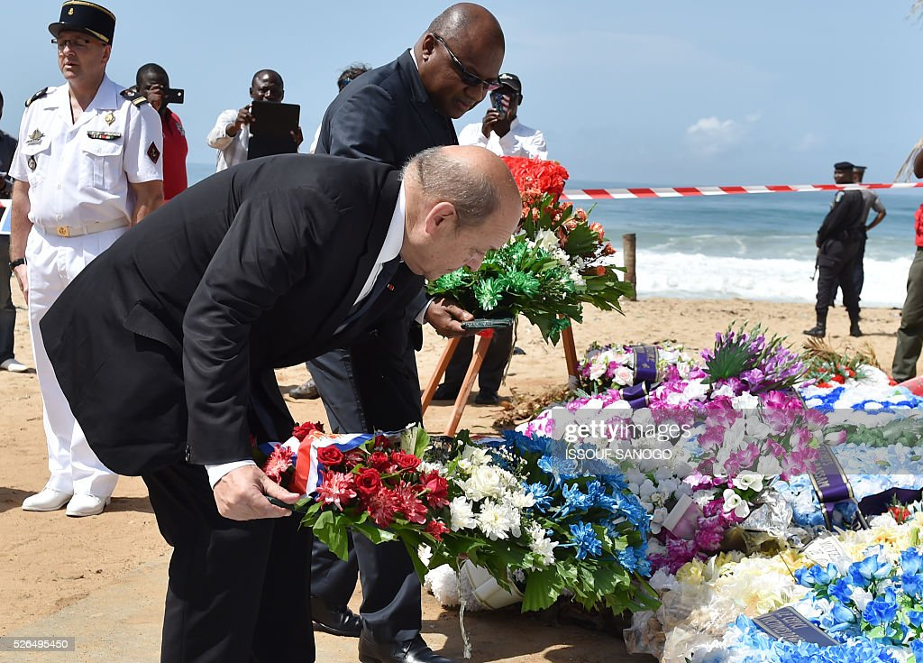 French Defence minister Jean-Yves Le Drian (C) and the representative of Ivory Coast's defence minister, Jean Paul Malan (R), lay wreaths of flowers in front of the Hotel Etoile du Sud on April 30, 2016 which was hit by a jihadist attack in March that left 19 people dead. France will increase the number of its troops in Ivory Coast, Defence Minister Jean-Yves Le Drian said on a trip to the African nation which hosts a regional base for French forces. / AFP / ISSOUF