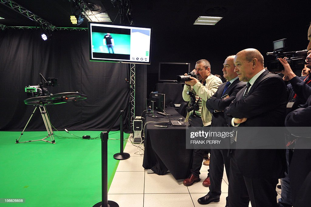 French Defence minister Jean-Yves Le Drian (R) watches a demonstration of a drone used to previsualize camera effects during the inauguration of the Technicolor research and development centre in Cesson-Sevigne near the western city of Rennes, on November 22, 2012. AFP PHOTO FRANK PERRY