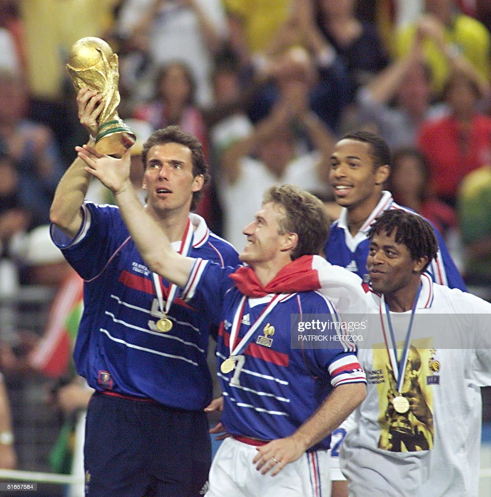 French defender Laurent Blanc (L) and captain <a gi-track='captionPersonalityLinkClicked' href=/galleries/search?phrase=Didier+Deschamps&family=editorial&specificpeople=213607 ng-click='$event.stopPropagation()'>Didier Deschamps</a> celebrate with the FIFA Trophy 12 July at the Stade de France in Saint-Denis, near Paris, after France defeated Brazil 3-0 in the 1998 Soccer World Cup final match to win its first-ever World title.