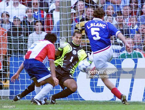 French defender Laurent Blanc scores as Paraguay's goalkeeper Jose Luis Chilavert dives 28 June at the Felix Bollaert stadium in Lens northern France...