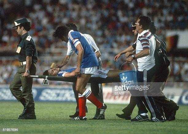 French defender Patrick Battiston is carried off the field on a stretcher as captain Michel Platini tries to comfort him during the World Cup...