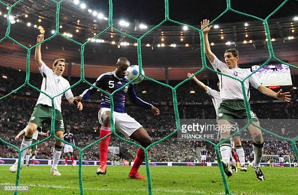 French defender William Gallas scores against Irish forward Keith Andrews and Irish defender Kevin Kilbane during the World Cup 2010 qualifying...