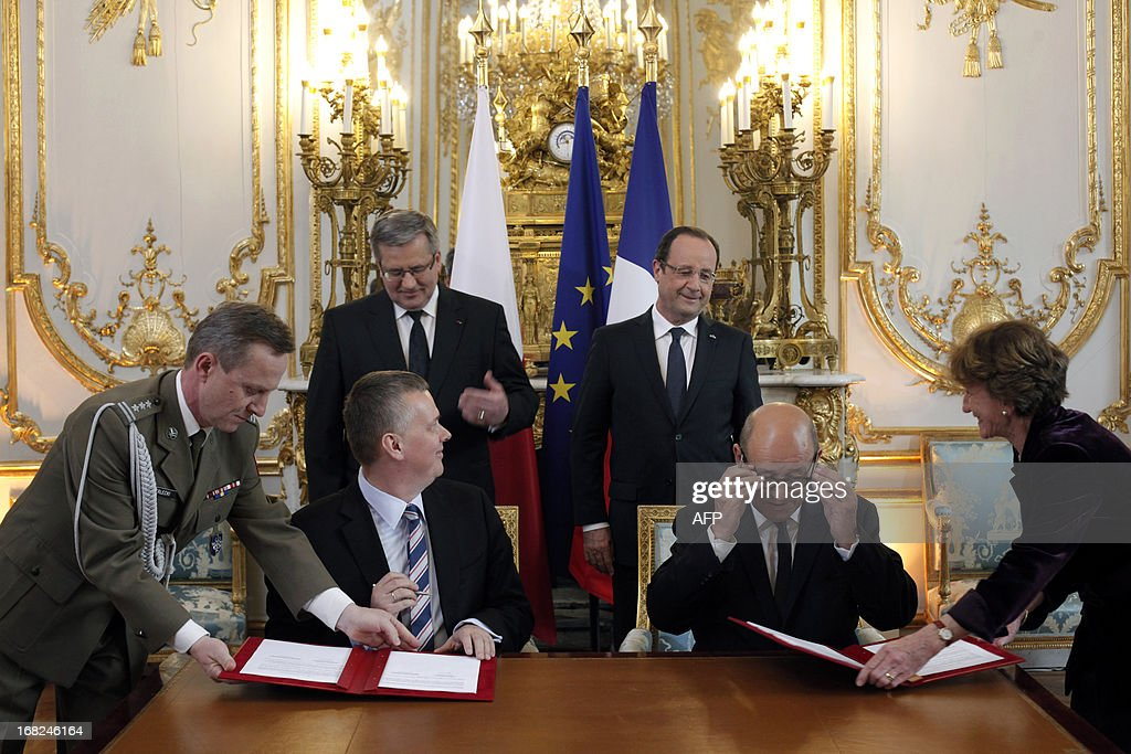 French Defense Minister Jean Yves Le Drian (front R) and his Polish counterpart Thomasz Siemoniak (front L) prepare to sign an agreement as French President Francois Hollande (back R) and his Polish counterpart Bronislaw Komorowski, smile at the Elysee presidential Palace in Paris on May 7, 2013, as part of Komorowski's two-day visit to France. AFP PHOTO / POOL / Thibault Camus