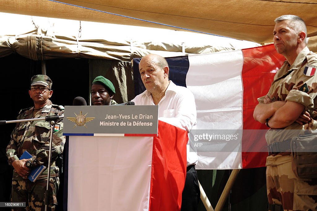 French Defense Minister Jean-Yves le Drian (C), flanked by a Niger officer (L), Malian army chief of staff General Ibrahima Dahirou Dembele (2nd L) and French army Colonel Mistral (R), commanding the Gao operations, addresses soldiers during a visit to Gao on March 7, 2013. French Defence Minister Jean-Yves Le Drian was in Mali on Thursday to meet French troops fighting Islamist rebels, the ministry said. He was to visit several cities, including the capital Bamako, and was due in the northern city of Gao at mid-day.