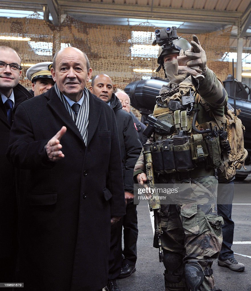 French Defense Minister Jean-Yves Le Drian (L) listens to explanations from a member of the French special forces on January 18, 2013 during a visit to the sniper commando base in the northwestern French town of Lanester.