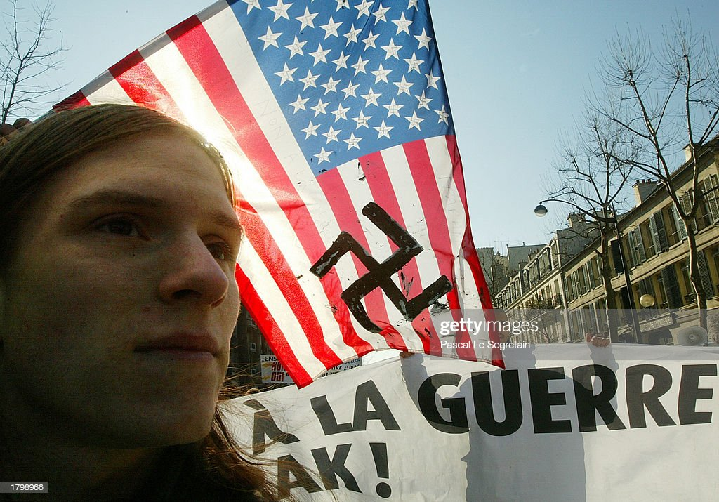 A French demonstrator marches in front of an American flag with swastika painted on it during a rally for peace February 15, 2003 in Paris. Thousands people demonstrate against a possible war on Iraq took to the streets in Paris.