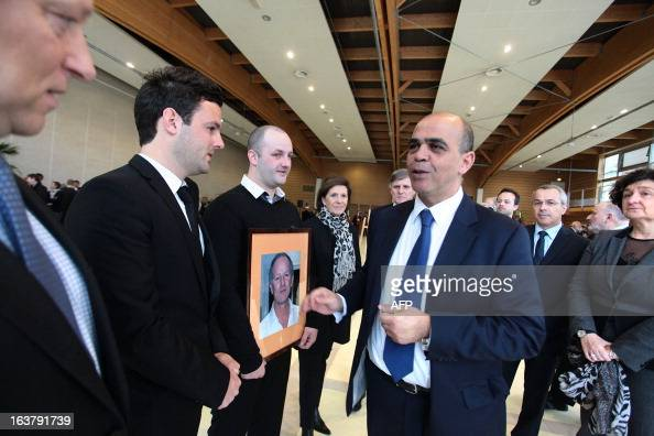 French Deputy Minister in charge of Veteran Affairs Kader Arif speaks on March 16 2013 to unidentified relatives of Yann Desjeux a former French...