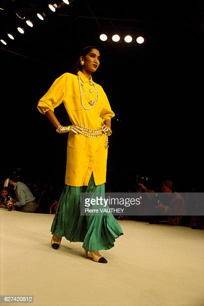 French design house Chanel shows its 1986 springsummer women's readytowear line in Paris The model is wearing a yellow tunic blouse over a green skirt