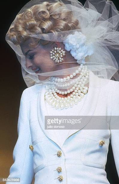 French design house Chanel shows its 1991 women's springsummer haute couture line Model Linda Evangelista is wearing a sheer veil and beaded necklace...