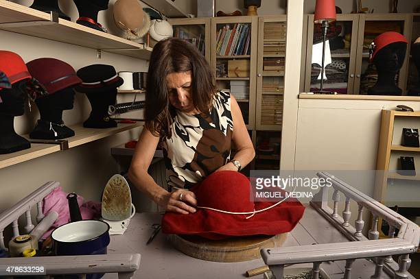 French designer hat and jewelry maker and artist Valerie Drevon puts a wicker around a felted a hat at her studio in Vincennes outside Paris on June...