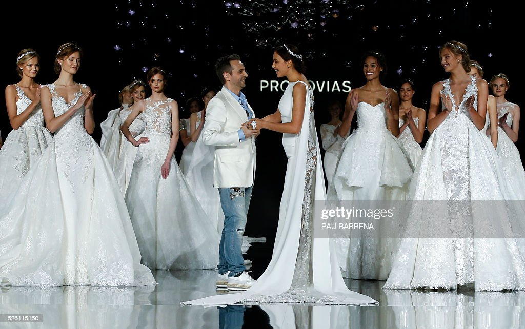 French designer Herve Moreau (C L) cheers Russian model Irina Shayk (C R) at the end of the presentation of the Pronovias 2016 collection during the last day of the Barcelona Bridal Week in Barcelona, on April 29, 2016. / AFP / PAU