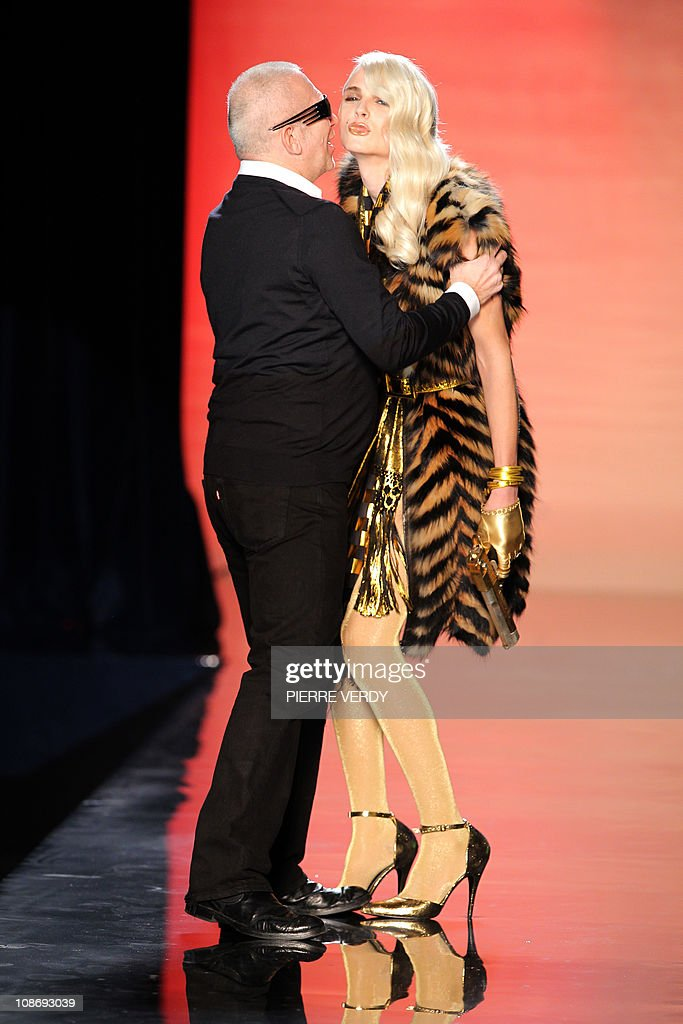 French designer Jean-Paul Gaultier kisses Australian model Andrej Pejic holding a gun at the end of his Men's fall-winter 2011-2012 ready-to-wear collection show on January 20, 2011 in Paris.