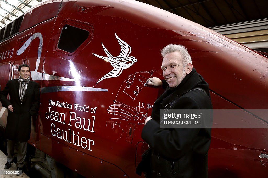 French designer Jean-Paul Gaultier (R) poses as he signs a drawing and his autograph on a Thalys train at the Gare du Nord railway station in Paris, on February 6, 2013, as part of the launch of the exhibition 'The Fashion World of Jean Paul Gaultier, from the Sidewalk to the Catwalk', which will run at the Kunsthal museum from February 10 to May 12, 2013 in Rotterdam. At right is seen French CEO of Thalys International, Franck Gervais.