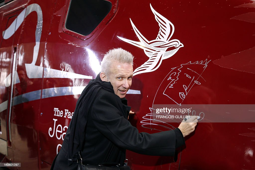 French designer Jean-Paul Gaultier poses as he signs a drawing and his autograph on a Thalys train at the Gare du Nord railway station in Paris, on February 6, 2013, as part of the launch of the exhibition 'The Fashion World of Jean Paul Gaultier, from the Sidewalk to the Catwalk', which will run at the Kunsthal museum from February 10 to May 12, 2013 in Rotterdam.