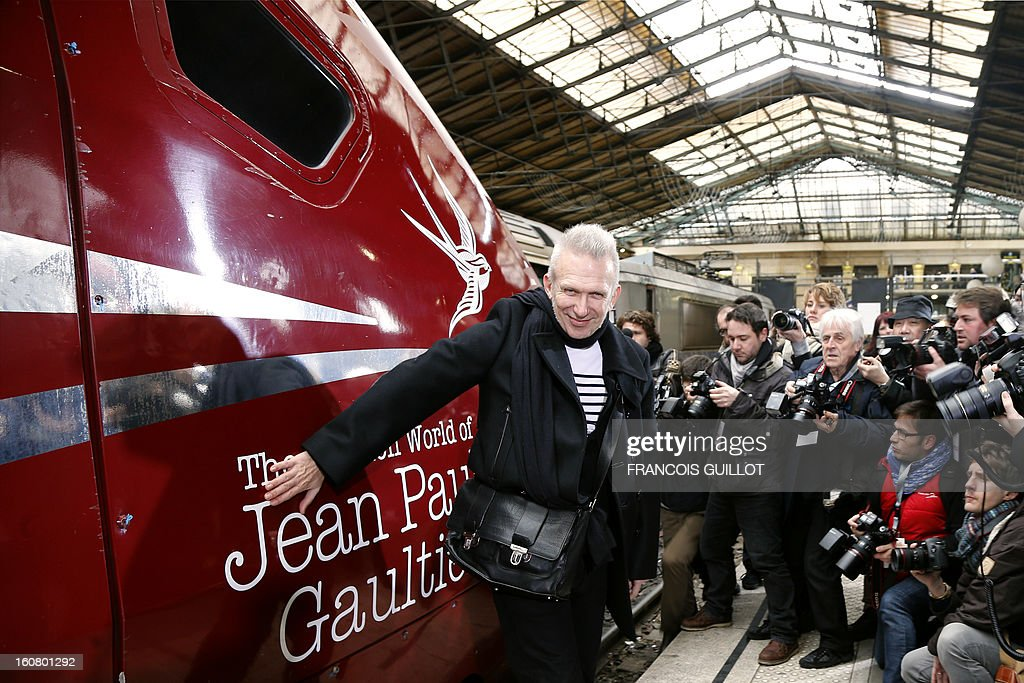 French designer Jean-Paul Gaultier (C) poses in front of a Thalys train at the Gare du Nord railway station in Paris, on February 6, 2013, as part of the launch of the exhibition 'The Fashion World of Jean Paul Gaultier, from the Sidewalk to the Catwalk', which will run at the Kunsthal museum from February 10 to May 12, 2013 in Rotterdam. On this occasion, Gautier signed a drawing and his autograph on a Thalys train painted with blue sailor stripes. AFP PHOTO FRANCOIS GUILLOT