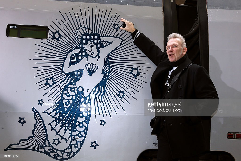 French designer Jean-Paul Gaultier poses on a platform in front of a Thalys train at the Gare du Nord railway station in Paris, on February 6, 2013, as part of the launch of the exhibition 'The Fashion World of Jean Paul Gaultier, from the Sidewalk to the Catwalk', which will run at the Kunsthal museum from February 10 to May 12, 2013 in Rotterdam. On this occasion, Jean-Paul Gaultier signed a drawing and his autograph on a Thalys train painted with blue sailor stripes. AFP PHOTO FRANCOIS GUILLOT