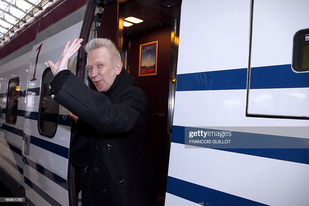 French designer Jean-Paul Gaultier waves aboard a Thalys train painted with blue sailor stripes at the Gare du Nord railway station in Paris, on February 6, 2013, as part of the launch of the exhibition 'The Fashion World of Jean Paul Gaultier, from the Sidewalk to the Catwalk', which will run at the Kunsthal museum from February 10 to May 12, 2013 in Rotterdam. On this occasion, Jean-Paul Gaultier signed a drawing and his autograph on a Thalys train painted with blue sailor stripes. AFP PHOTO FRANCOIS GUILLOT