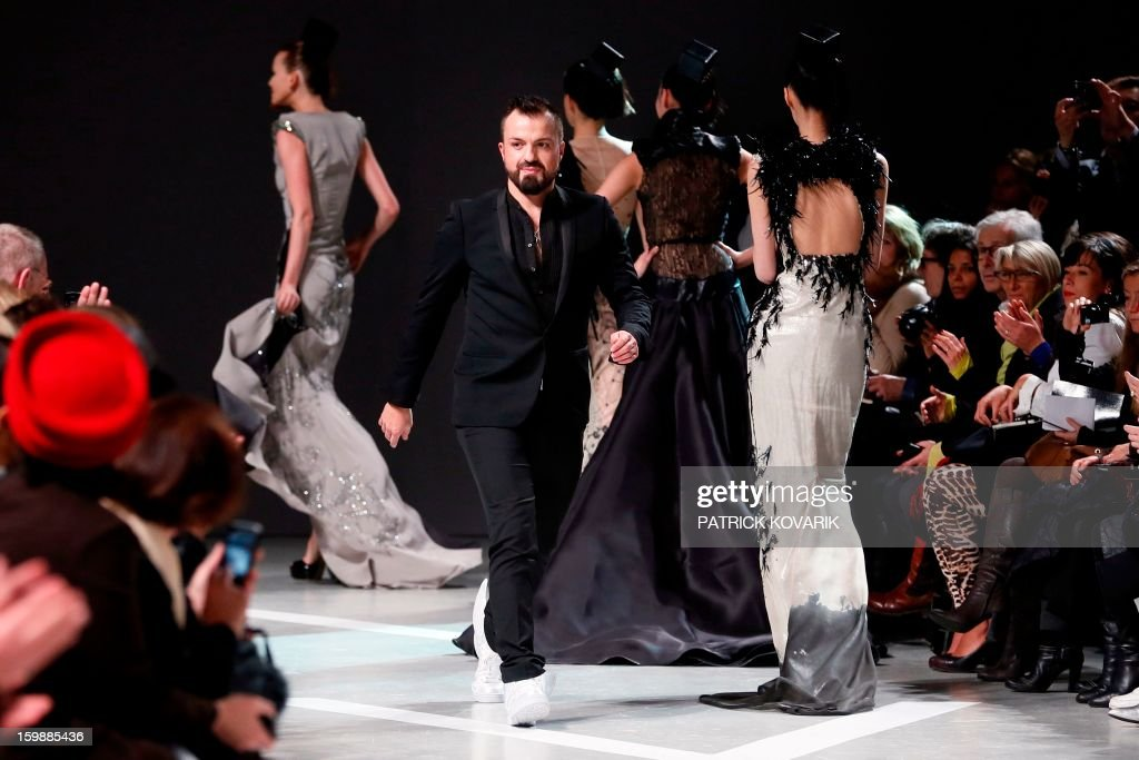 French designer Julien Fournie walks past models as he acknowledges the public at the end of his Haute Couture Spring-Summer 2013 collection shows on January 22, 2013 in Paris. AFP PHOTO / PATRICK KOVARIK
