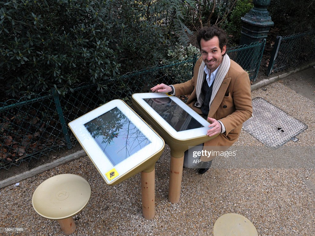 French designer Mathieu Lehanneur poses with a 'table Play', a video game prototype he designed, proposed by the global outdoor advertising leader JCDecaux during its presentation in a Paris' garden on January 31, 2103. Forty Table Play's prototypes are tested on the Parisian territory as part of the 'smart urban street furniture' (Mobilier Urbain Intelligent) project bid launched by Paris city hall.