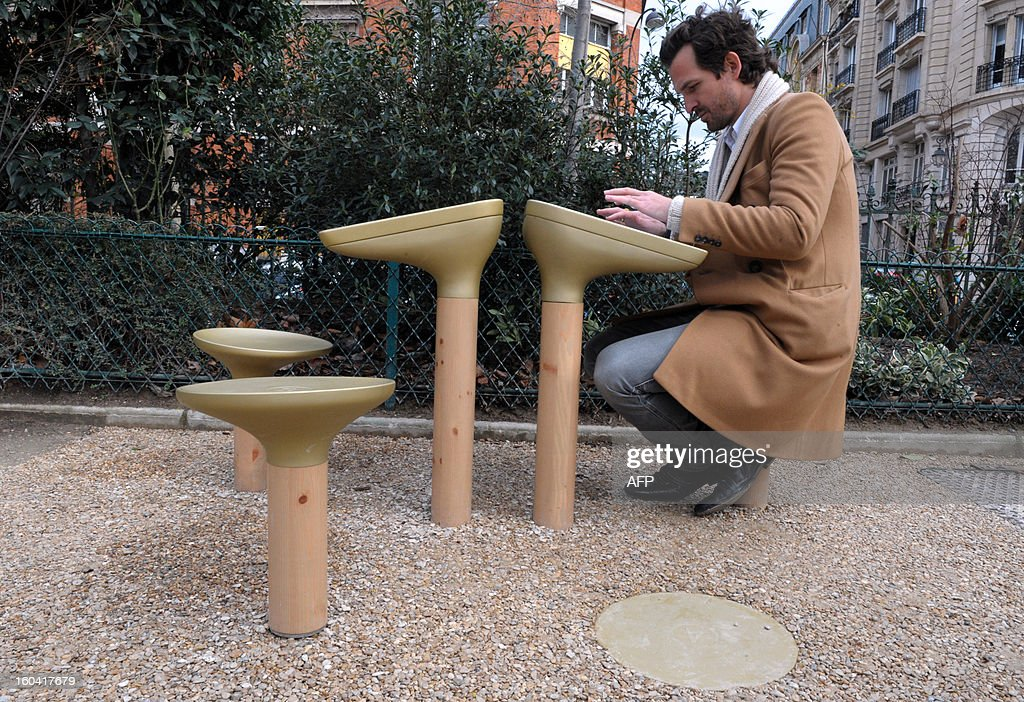 French designer Mathieu Lehanneur poses with a 'table Play', a video game prototype he designed, proposed by the global outdoor advertising leader JCDecaux during its presentation in a Paris' garden on January 31, 2103. Forty Table Play's prototypes are tested on the Parisian territory as part of the 'smart urban street furniture' (Mobilier Urbain Intelligent) project bid launched by Paris city hall. AFP PHOTO / ERIC PIERMONT