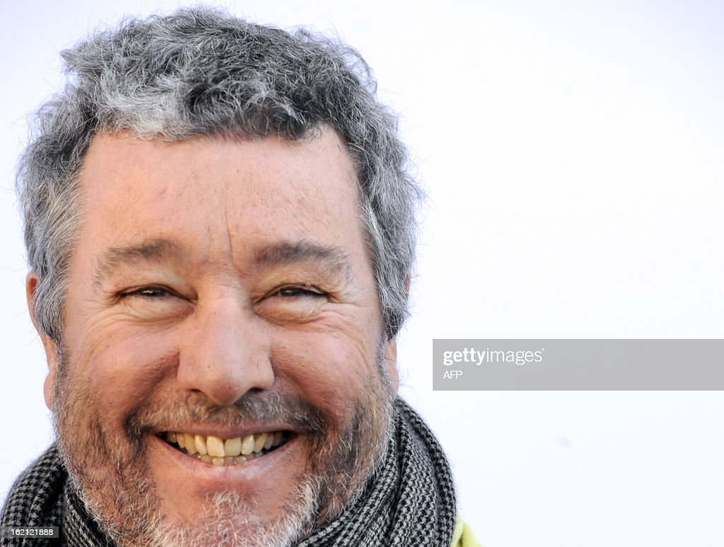 French designer Philippe Starck smiles on February 19, 2013 while posing during the presentation at Bordeaux's Town Hall of his latest creation, 'the Pibal', the city's new hybrid urban bicycle. The bikes, manufactured by Peugeot, should be available in September 2013. AFP PHOTO / JEAN PIERRE MULLER
