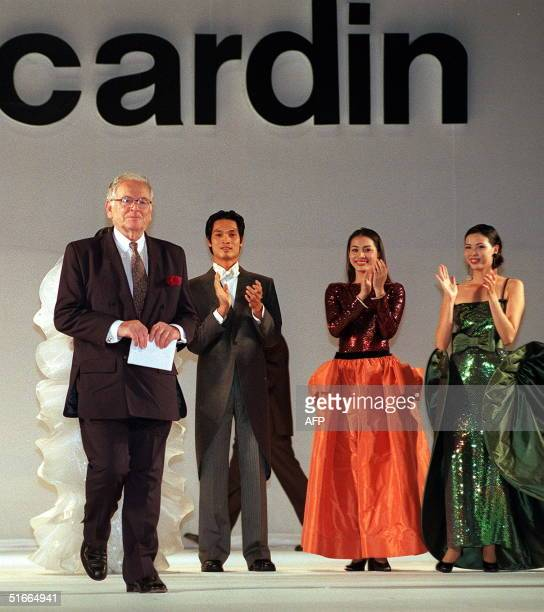 French designer Pierre Cardin enters the catwalk as Vietnamese models clap at the end of a show held late evening 27 October 1999 in Ho Chi Minh City...