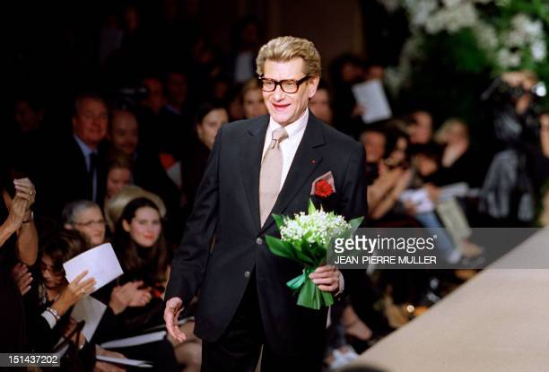 French designer Yves Saint Laurent comes on the catwalk with a bunch of flowers for supermodel Laetitia Casta wearing his 'Just married' suit at the...