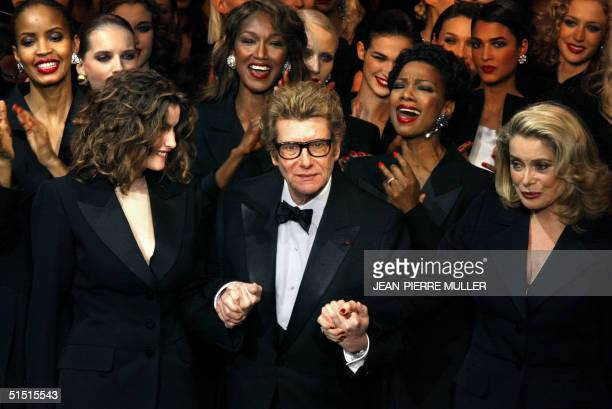 French designer Yves SaintLaurent salutes the crowd with French model Laetitia Casta and French actress Catherine Deneuve at the Centre Georges...