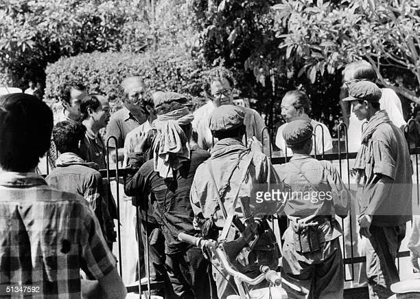 French diplomat talks with Khmer Rouge leaders at the gate of the French embassy in Phnom Penh 17 April 1975 where hundreds of people found refuge...