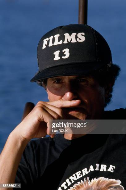 French director Claude Lelouch pendant wears a cap from his production house Films 13 on the set of his film Itineraire d'un Enfant Gate