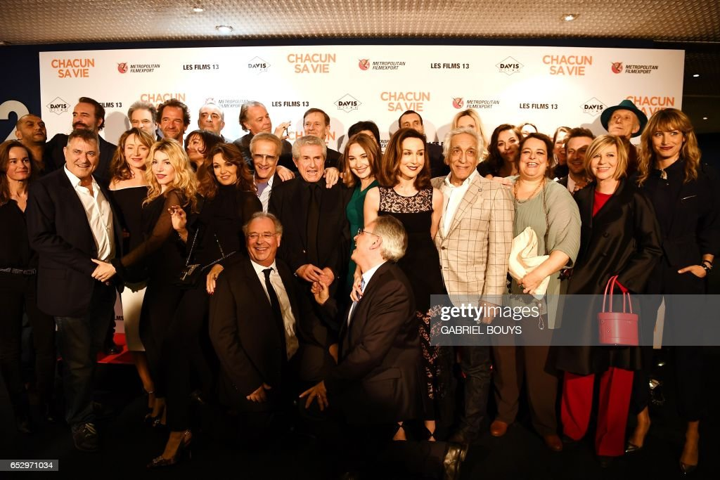 French director Claude Lelouch (C) poses with members of the cast during the photocall for the premiere of his film 'Chacun Sa Vie' in Paris on March 13, 2017. /