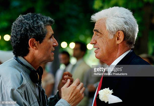 French director Claude Lelouch talks with actor JeanPaul Belmondo on the set of the 1995 French film Les Miserables