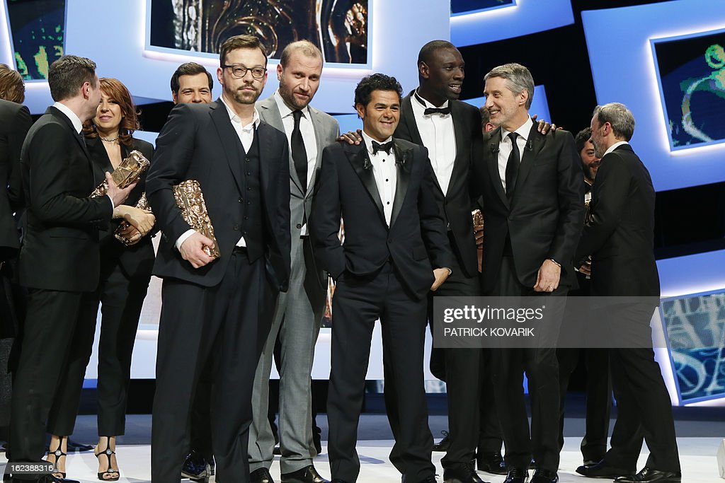 French director Cyril Mennegun poses with his trophy beside (from L) Belgian actor Francois Damiens, French actor and President of the ceremony Jamel Debbouze, French actor Omar Sy and French actor and Master of Ceremony Antoine de Caunes at the end of the 38th Cesar Awards ceremony on February 22, 2013 at the Chatelet theatre in Paris. AFP PHOTO / PATRICK KOVARIK